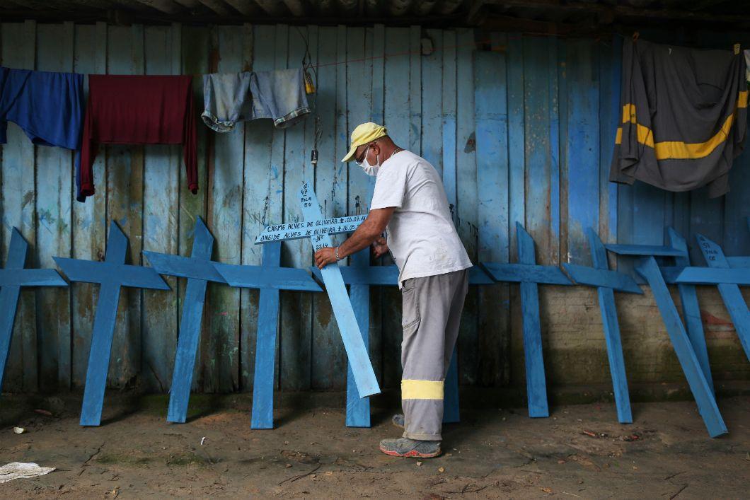 Un homme travaillant au cimetière Nossa Senhora à Manaus, au Brésil, termine de fabriquer des croix pour les enterrements, le 9 mai 2020. La gestion désastreuse de la crise du coronavirus par son président Jair Bolsonaro, qui a notamment tenté de saborder les mesures prises pour l'enrayer, est fortement pointée du doigt. Avec plus de 142.000 décès, le Brésil déplore désormais le deuxième nombre le plus élevé de mortsau monde, derrière les États-Unis.
