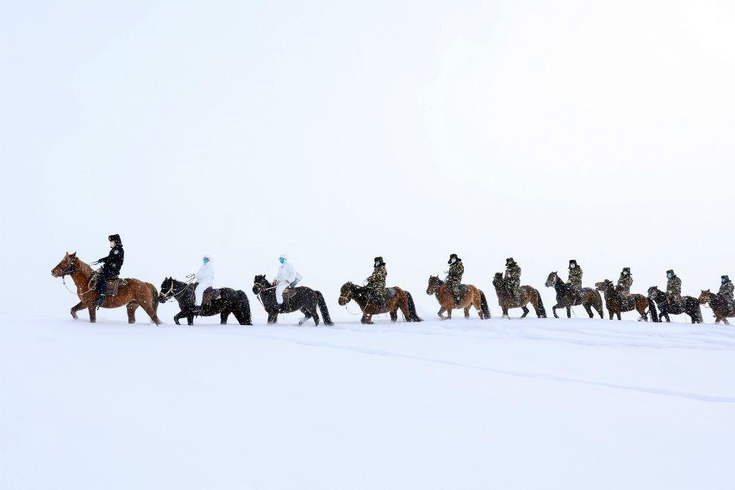 Apparu en décembre 2019 dans la ville du Wuhan, au centre de la Chine, le virus responsable de la maladie infectieuse respiratoire appelée Covid-19 se propage en quelques semaines sur le territoire chinois. Sur cette photo prise le 19 février 2020, des policièr·es portant desmasques protecteurs se rendent à cheval dans le territoire éloigné d'Altay, dans la région du Xinjiang, en Chine, afin d'y observer sa propagation.