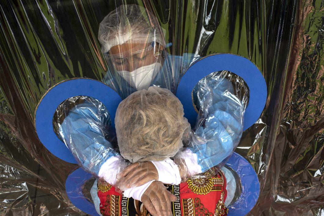 Dans une maison de retraite duSalvador, une jeune femme embrasse sa tante à travers un rideau de protection, le 11 septembre 2020. Les personnes âgées, particulièrement vulnérables face au virus, sont les principales victimes de la pandémie.
