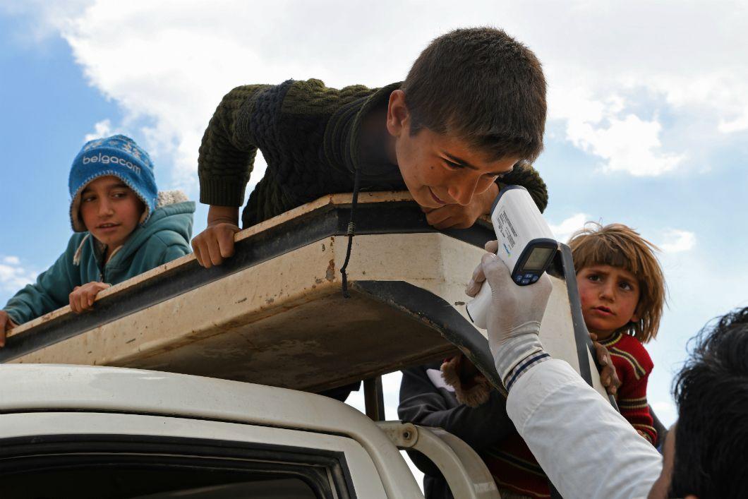 De l'Italie à la Chine en passant par les États-Unis, on prend la température pour détecter des signes de fièvre, l'un des symptômes du Covid-19. Le 17 mars 2020, dans le camp de déplacés syriens Deir al-Ballut de la province d'Alep, le long de la frontière avec la Turquie, le personnel médical informe la population des dangers du virus et tented'empêcher sa propagation sur cesol déjà frappé par la guerre.